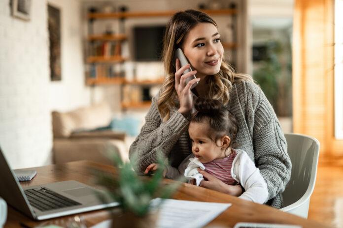 Lächelnde Mutter hält kleine Tochter in ihrem Schoß, während sie zu Hause telefoniert.