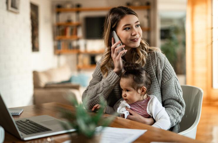 Madre sonriente sosteniendo a su hija pequeña en su regazo mientras habla por teléfono en casa.