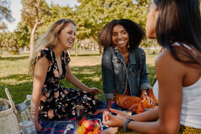 Smiling multiracial female friends having fun at picnic in the park - group of healthy friends having a picnic