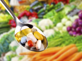 spoon with variety of pills, dietary supplements on blurred vegetables background