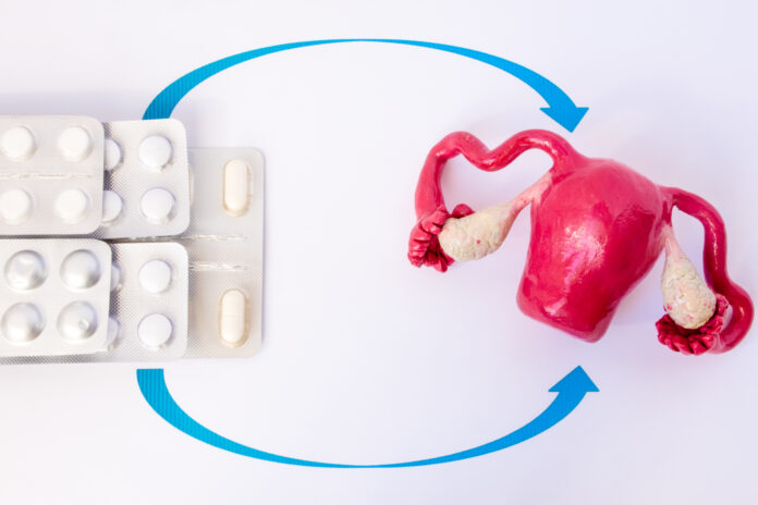 Stack blisters with pills and capsules inside pointed arrows on model of uterus with ovaries. Concept photo of hormone replacement therapy in gynecology at menopause, climax, removed ovaries