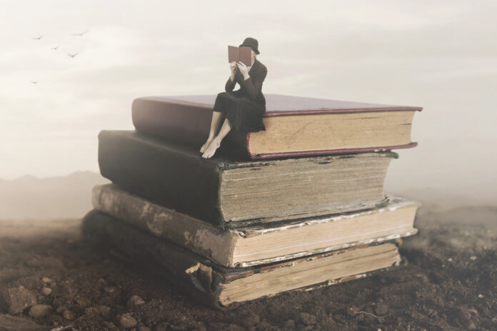 Surreal image of a woman reading sitting on top of a book