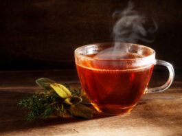 tea freshly brewed in a glass cup and some herbs on a dark rustic wooden background, healthy hot drink against cold and flu, copy space, selected focus