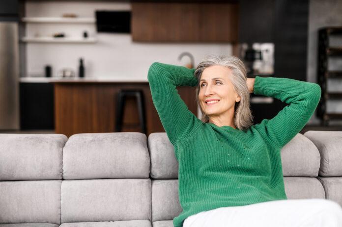The winsome senior lady is resting on the comfortable couch at home, charming elderly woman in casual wear put her hands behind her head and daydreaming in relaxed atmosphere, wellbeing concept