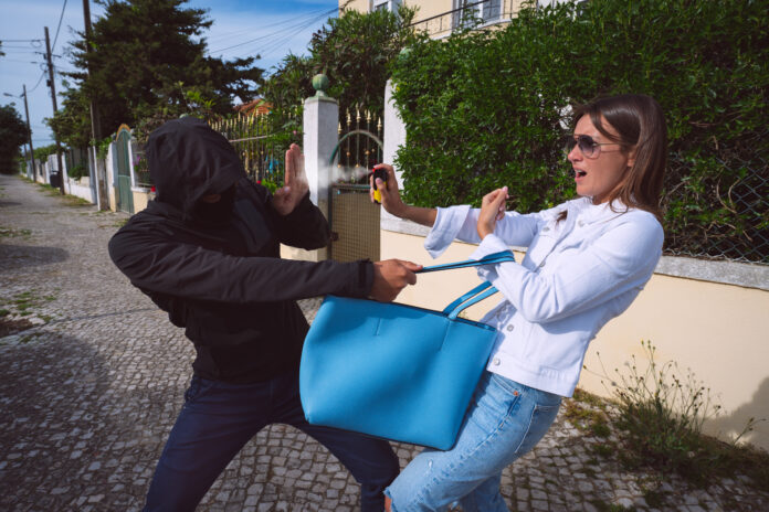 Thief or robber in the mask trying to steal woman's bag outdoors. Woman using pepper spray or tear gas for self defence. Woman defending herself against thief. High quality photo