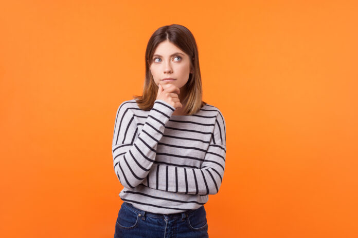 Think up plan. Portrait of pensive woman with brown hair in long sleeve striped shirt standing holding hand on chin and looking up, thinking intensely. indoor studio shot isolated on orange background
