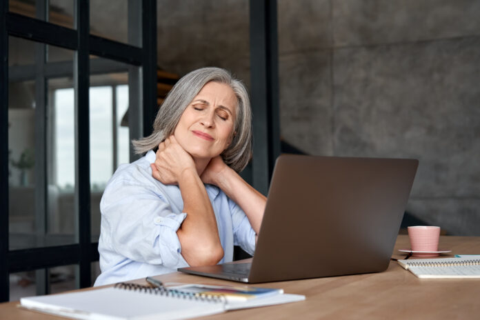 Müde gestresst alten reifen Business-Frau leidet unter Fibromyalgie Nackenschmerzen arbeiten im Büro sitzen am Tisch. Overworked Senior mittleren Alters Dame massiert Hals Gefühl verletzt Schmerz von sitzenden Job