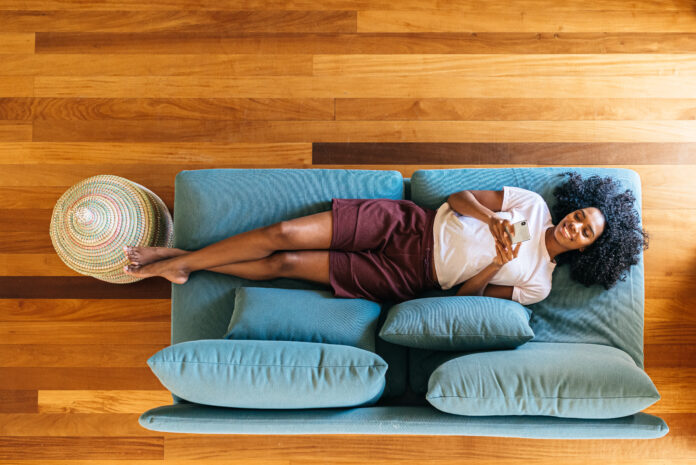 Top view of African American lady in casual wear resting on blue sofa and smiling while surfing on mobile phone at home