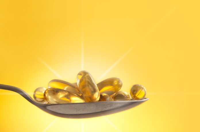 Vitamin D capsules on a spoon in sunlight