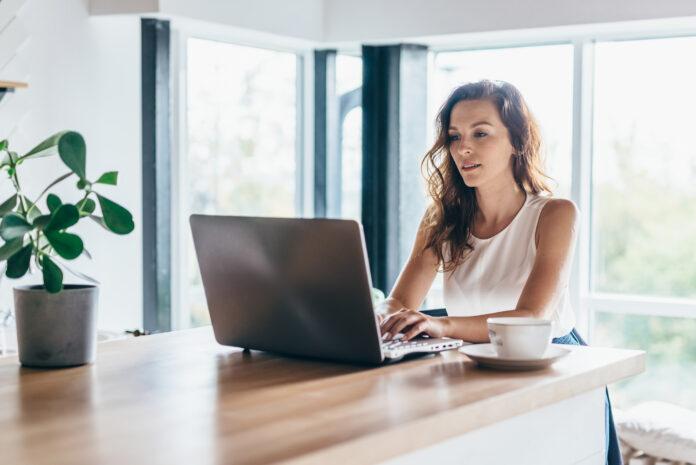 Frau, die einen Laptop benutzt, während sie zu Hause sitzt.