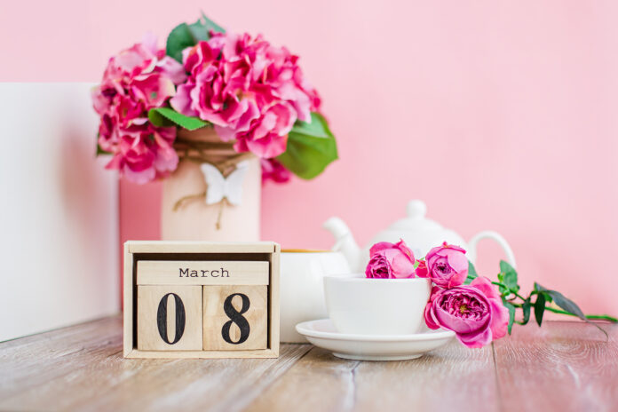Women's Day. March 8 tree calendar, International Women's Day, decorated with pink and purple flowers on a pink background. Good morning cup of tea or coffee.