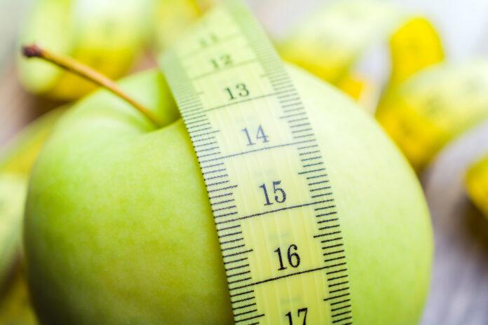 Gelbes Maßband auf grünem Apfel liegend - Leben Gesundes Konzept