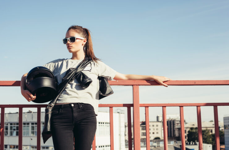 Young female biker holding a motorcycle helmet. Outdoor lifestyle portrait
