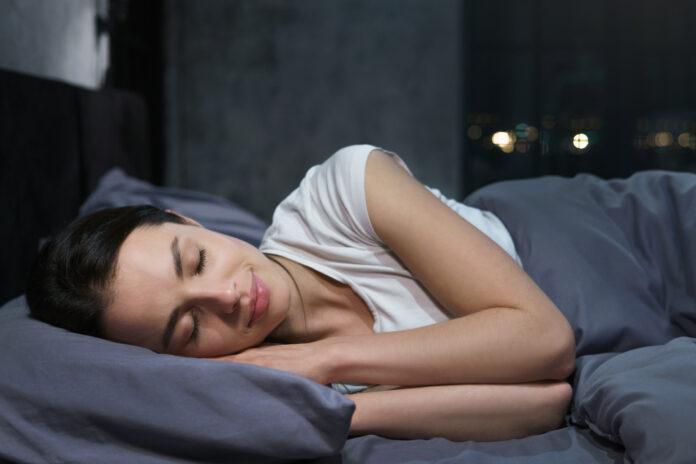 Jeune femme dormant paisiblement dans sa chambre la nuit, se relaxant