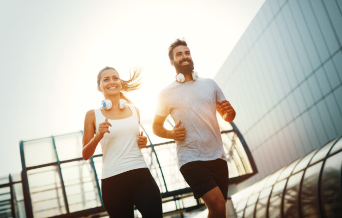 Young fitness couple running together in urban area