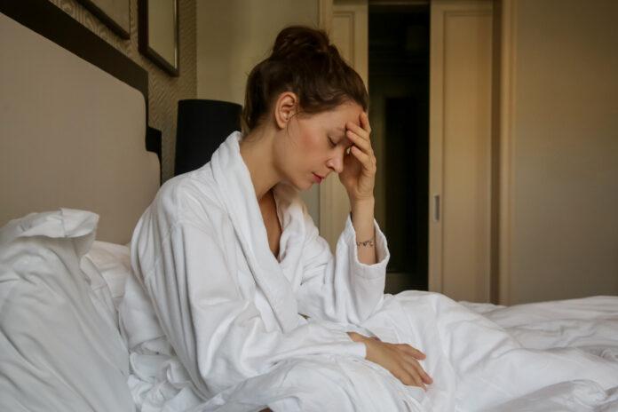 Junge traurige Frau, die im Bett sitzt, Depression, Angst, Beziehungsprobleme, Migräne oder morgendliche Übelkeit Konzept