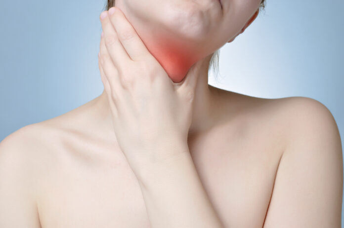 Young woman holding her painful neck