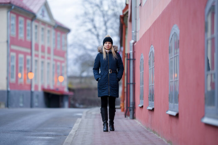 Young woman in warm clothes slowly walking at old town center in cold day in evening. Front view. City life.