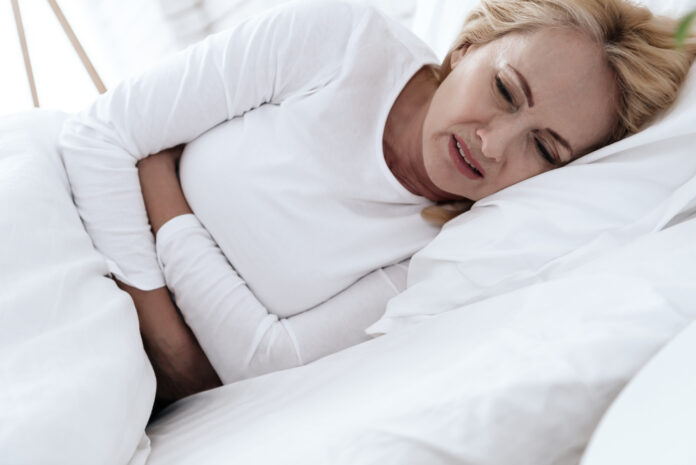 A white woman has a stomach ache. She feels bad and uncomfortable, then that it hurts. She holds her hands in her sore spot.