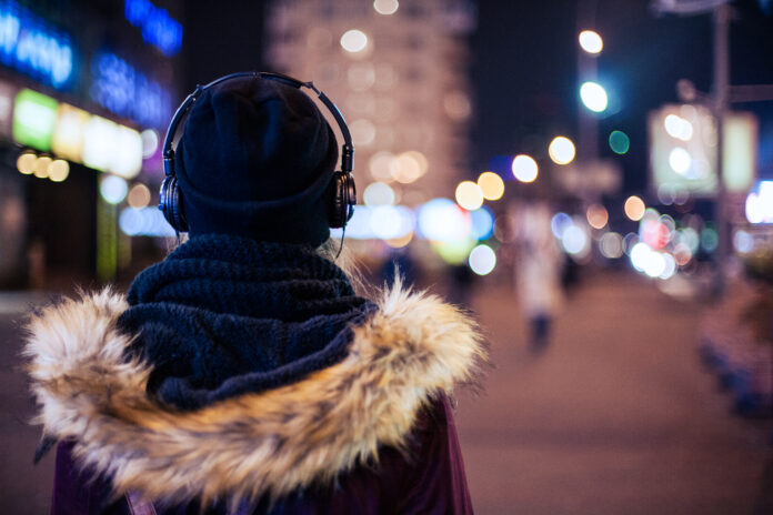 Back view of a hipster girl walking through night city street  listening to the music
