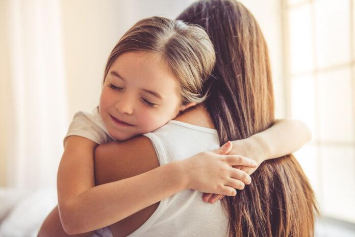 Schöne junge Frau und ihre charmante kleine Tochter sind umarmt und lächelnd