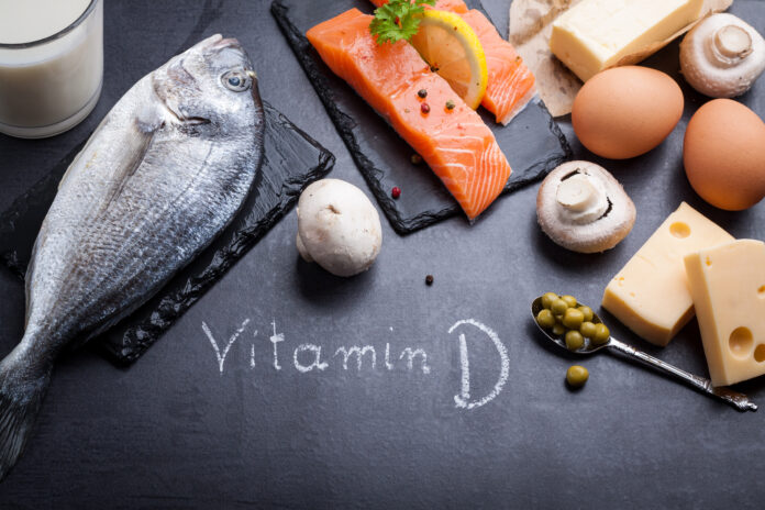 Stół z czarnego łupka z produktem bogatym w witaminę D i omega 3. Słowo witamina D napisane białą kredą.