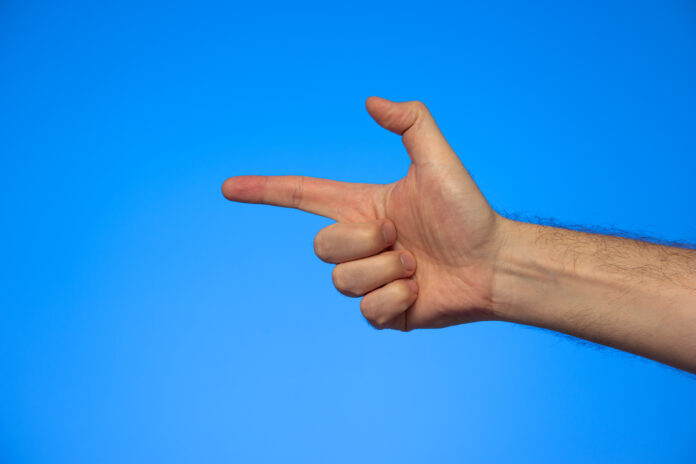 Caucasian male hand making a fake pistol gesture studio shot isolated on blue.