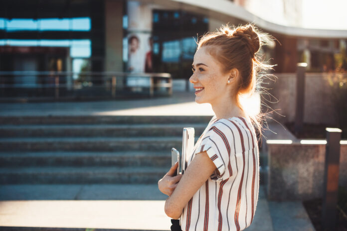 Cheerful caucasian girl with red hair and freckles is holding a tablet and looking away staying in front of a building