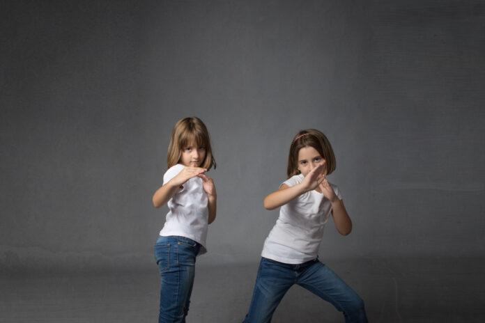 Kinder in einer Karate-Verteidigung, dunkler Hintergrund