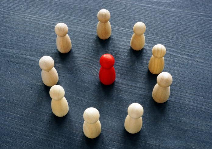 Kreis aus Holzfiguren und roter Figur. Konzept der Diskriminierung oder Belästigung.
