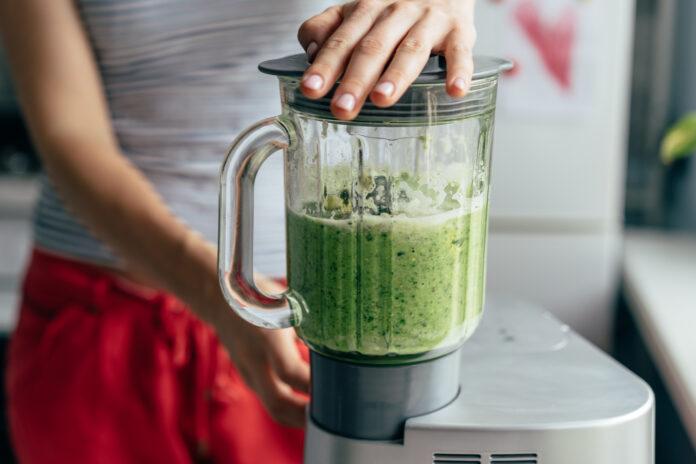 Nahaufnahme Mixerprozess. Zubereitung eines grünen Abend-Smoothies. Mischen in einer Blender-Schüssel.