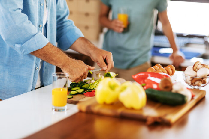 Close up of mature couple cooking a meal together at home