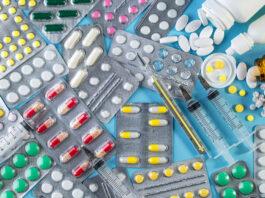 Verschiedene Medikamente in Tabletten, Ampullen, Fläschchen und in der Masse, medizinische Quecksilber-Thermometer und Spritze auf blauem Hintergrund. Medizin-Konzept. Pharmazeutische Blisterpackung. Packung mit Pillen und Tabletten.