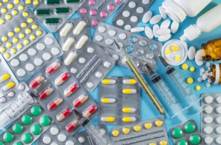 Różne leki w tabletkach, ampułkach, fiolkach i luzem, medyczne termometr rtęciowy i strzykawka na niebieskim tle. Medycyna pojęcie. Opakowanie farmaceutyczne blister. Opakowanie tabletek z tabletkami.