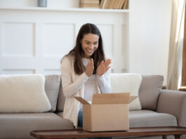 Excited young caucasian woman sit on sofa at home feel euphoric unbox internet order package, happy millennial female unpack box shopping online, satisfied with good quality product, delivery concept