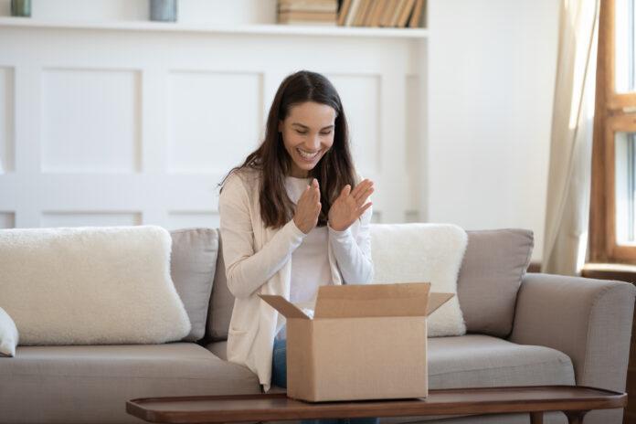 Spændt ung kaukasisk kvinde sidder på sofaen derhjemme føler sig euforisk unbox internet ordre pakke, glad millennial kvinde unpack boks shopping online, tilfreds med god kvalitet produkt, levering koncept
