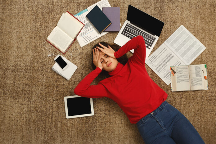 Exhausted student girl lying on the floor among textbooks, tests and gadgets, copy space. Woman holding head with hands, got tired while preparing for exams. Education and overworking concept