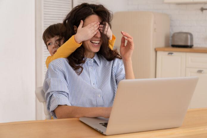 Donna freelance si siede vicino al tavolo nell'ufficio di casa durante il blocco, lavorando sul computer portatile. Bambino giocoso distrae dal lavoro, coprendo gli occhi della madre, bambino che fa rumore e chiede attenzione alla mamma impegnata