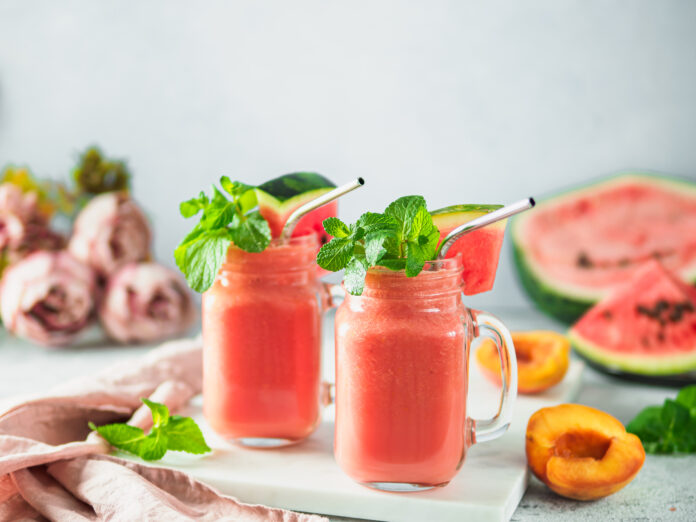 Freshly Blended Watermelon and Peach Smoothies in mason jar and metal straw. Copy space for text or design.