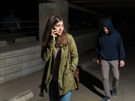 Frightened Hispanic woman talking on smartphone while looking back at criminal following her in parking lot