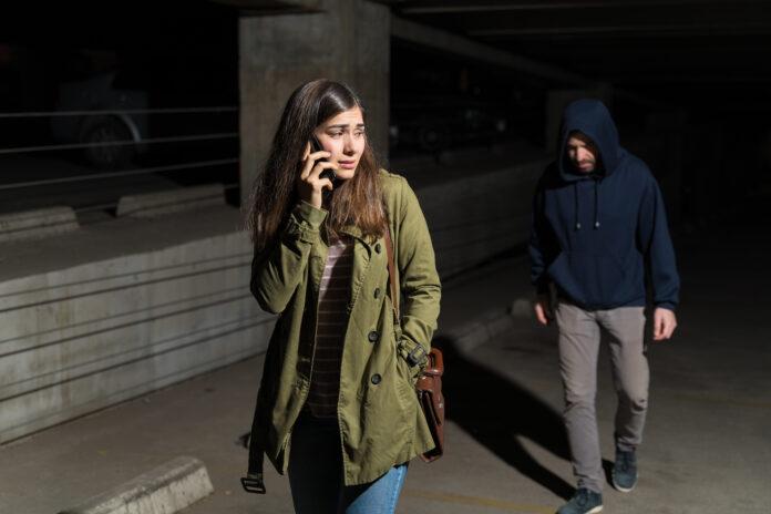 Une femme hispanique effrayée parle sur son smartphone tout en regardant derrière elle un criminel qui la suit dans un parking.