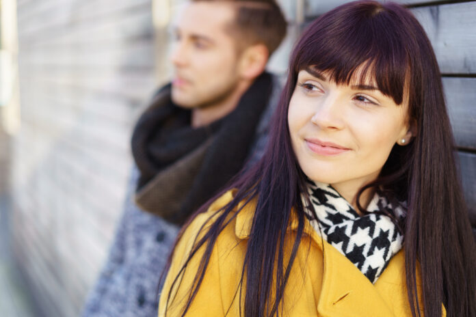 Handsome young woman leaning against a wooden wall grinning happily with a man in background