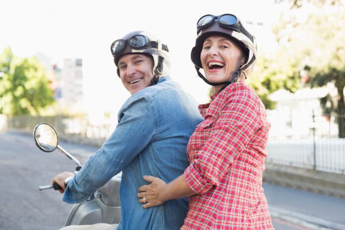 Feliz casal maduro a andar de scooter na cidade num dia de sol