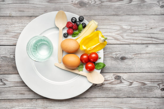 Interval fasting diet. Intermittent fasting concept represented with a plate and products on gray background. Healthy lifestyle. Fat loss concept. Top view