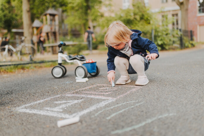 Kid playing on the street with some chalk