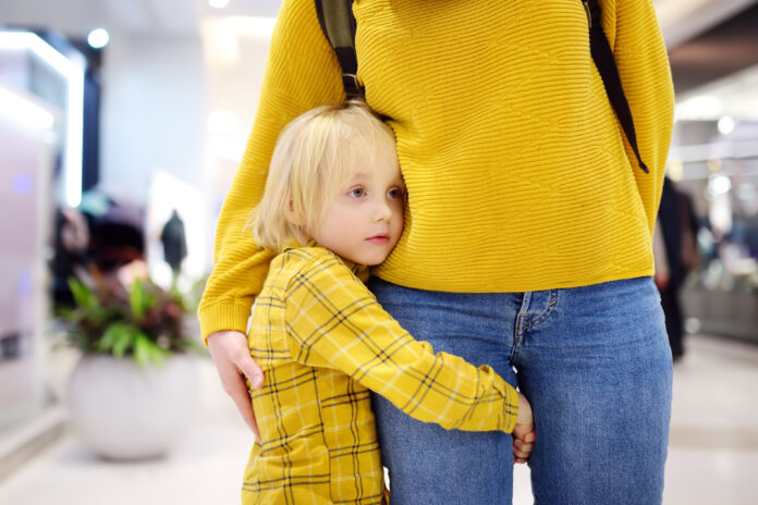Little boy embrased his mother. Shyness, fears, anxiety. Hyper-attachment to mother.
