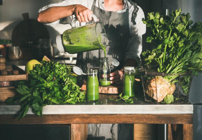 Préparation d'un smoothie vert détox à emporter. Femme en tablier de lin versant un smoothie vert du mixeur à une bouteille entourée de légumes et de verdure. Concept d'alimentation saine et de perte de poids.