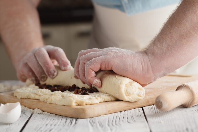 Male rolling cotage cheese strudel with raisin