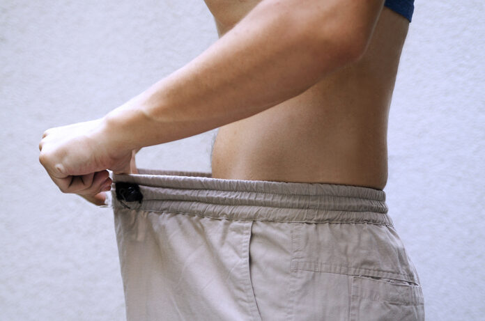 Man after diet comparing his waist size of trousers.Slim fit male body or genital issue.