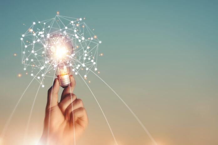 Nuevas ideas e imaginación Creatividad e inspiración Innovación tecnológica. Mano que sostiene la red digital del cerebro y la bombilla de la ciencia abstracta dentro de la conexión de red en el fondo del cielo.